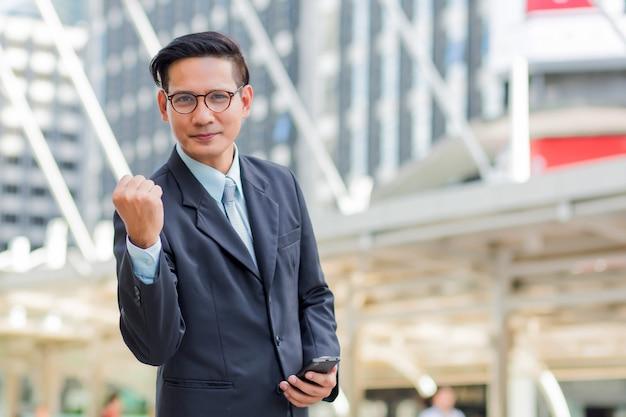 Célébrer le succès. heureux homme d'affaires en se tenant debout à l'extérieur avec l'immeuble de bureaux en arrière-plan Photo Premium