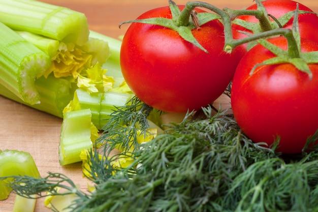 Céleri et tomates sur une planche à découper Photo Premium