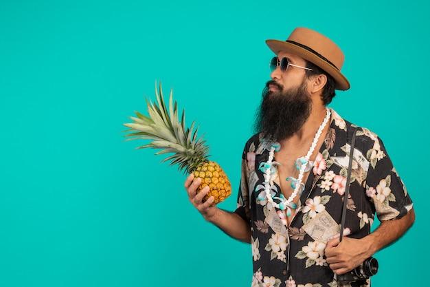 Celui d'un touriste avec une longue barbe coiffé d'un chapeau et tenant l'effet sur un bleu. Photo gratuit
