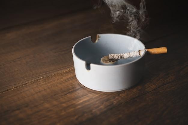 Cendrier avec cigarette sur la table de bois. Photo Premium