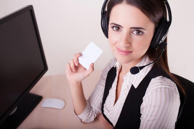 Centre d'appel femme avec casque montrant la carte de visite. Photo Premium