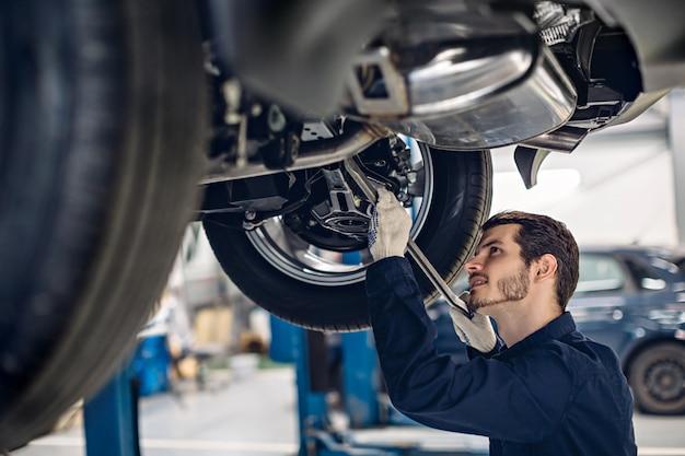 Centre De Service De Réparation Automobile. Mécanicien Examinant La Suspension D'une Voiture Photo Premium