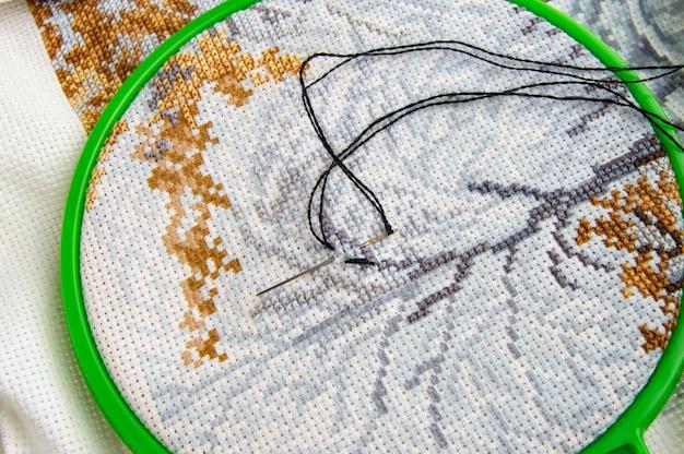 Cerceau à broder plat avec toile, fil à coudre brillant et aiguille à broder Photo Premium
