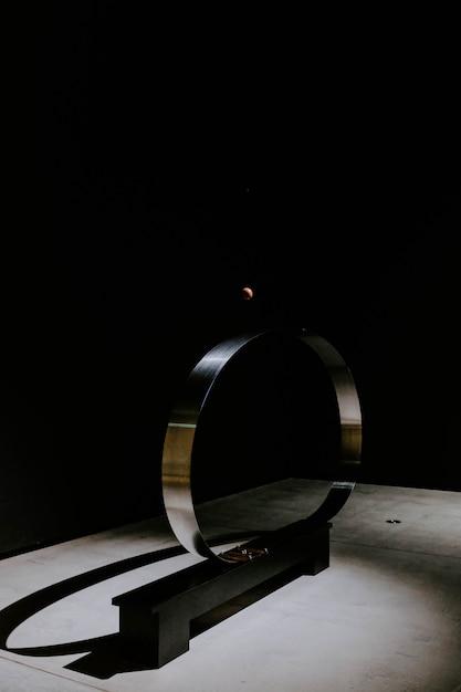 Cercle Métallique Devant Un Mur Noir Photo gratuit