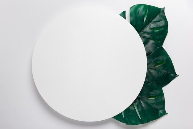 Cercle en papier fait main avec des feuilles à côté Photo gratuit