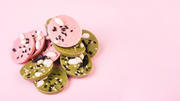 Cercles de chocolat vert et rose délicieux décorés avec des graines sur papier peint rose Photo gratuit