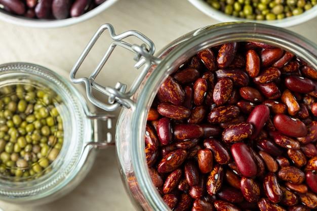 Les Céréales Ou Les Haricots Crus Dans Des Bocaux En Verre Se Bouchent. Nourriture Végétalienne Et Végétarienne. Photo Premium
