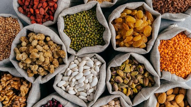 Céréales saines et fruits secs. bouchent la vue de dessus de petits sacs avec des graines de légumineuses sèches. différents types de haricots. grains naturels. Photo Premium