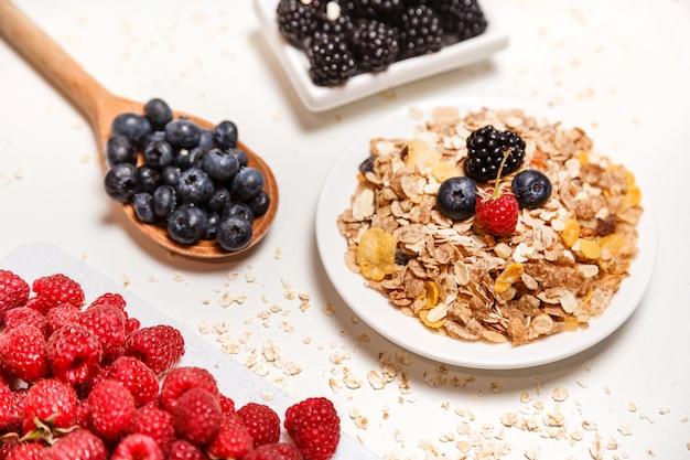 Céréales super food petit déjeuner avec des fruits frais isolés on white Photo Premium