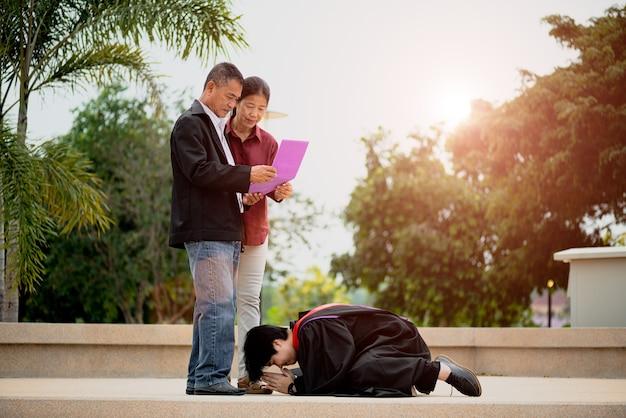 Cérémonie De Remise Des Diplômes. Femme Diplômée Donnant Un Certificat De Fin D'études à Ses Parents Photo Premium