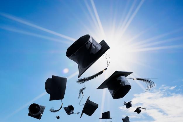 Cérémonie de remise des diplômes, graduation caps, chapeau jetés dans les airs avec abstrait ciel bleu. Photo Premium