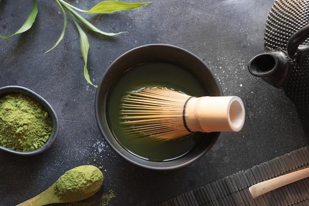 Cérémonie thé vert matcha et fouet en bambou sur tableau noir. vue de dessus. espace pour le texte. Photo Premium