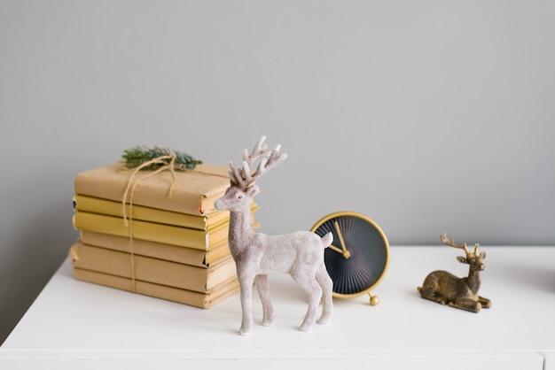 Cerf de noël dans un décor sur une étagère avec des livres et une horloge Photo Premium