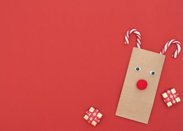Cerf De Noël En Sac à Provisions Artisanal Et Deux Cannes De Noël Avec Coffrets Cadeaux Sur Fond Rouge. Carte De Voeux De Nouvel An. Concept De Noël Et Du Nouvel An. Style Plat Avec Espace De Copie. Photo Premium
