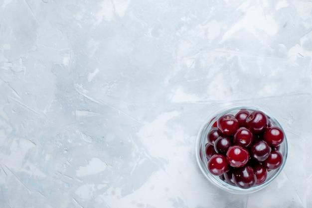 Cerises Aigres Fraîches à L'intérieur De La Petite Tasse En Verre Sur Blanc Clair Photo gratuit