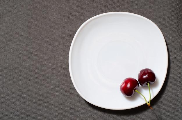 Cerises sur le bord d'une assiette vide sur le fond gris texture Photo Premium