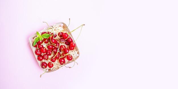 Cerises mûres rouges dans un panier en osier Photo Premium