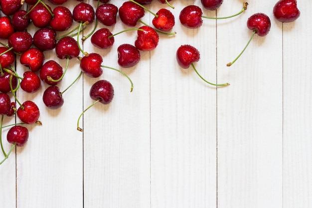 Cerises rouges sur bois blanc Photo gratuit