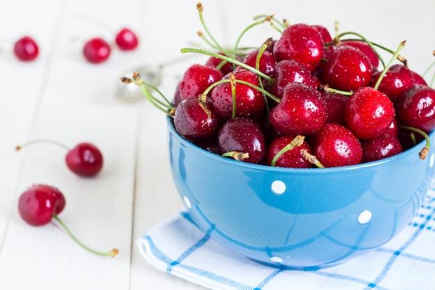 Cerises rouges dans un bol en bois blanc sur une serviette bleue Photo gratuit
