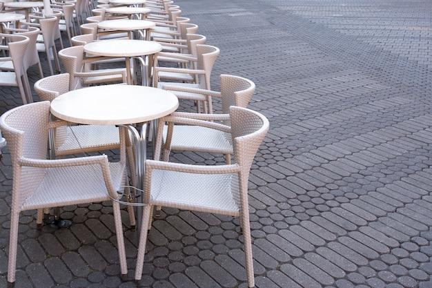 Un certain nombre de tables vides avec des chaises sont reliées par un câble antivol dans un café de la rue. Photo Premium