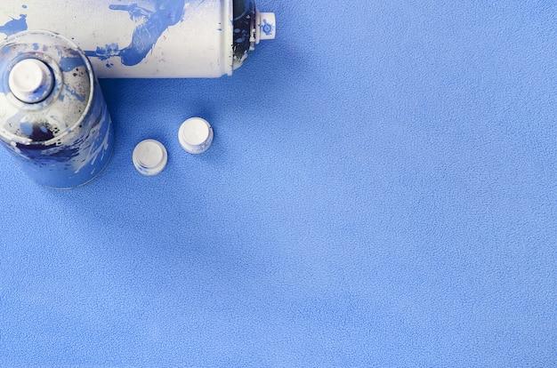 Certaines bombes aérosol bleues utilisées et des buses avec des gouttes de peinture se trouvent sur une couverture de tissu molletonné bleu clair et velu Photo Premium