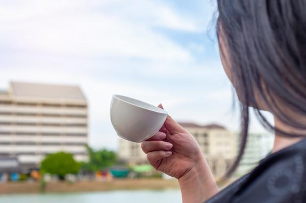 Certaines femmes avec une tasse de café sur le bâtiment de la tour floue Photo Premium
