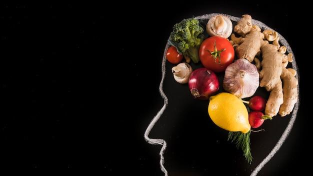 Cerveau humain fait avec des légumes sur le tableau noir Photo gratuit