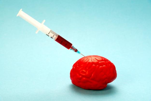 Cerveau rouge sur bleu avec une seringue nootropique. Photo Premium