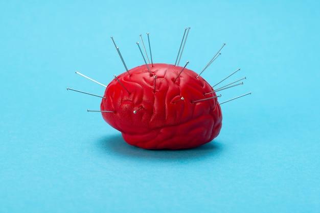 Cerveau rouge sur fond bleu avec des aiguilles injectées. Photo Premium