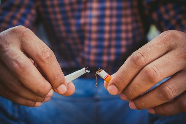 Cesser de fumer, des mains humaines brisant la cigarette Photo Premium