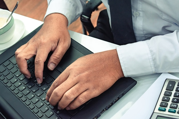 Cet homme d'affaires de carrière avec ordinateur portable avec calculatrice Photo Premium