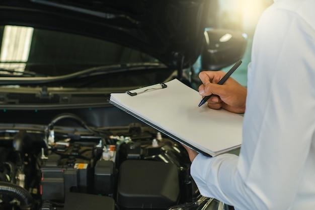 Cet homme de carrière saleman écrit une note d'inspection sur le bloc-notes Photo Premium