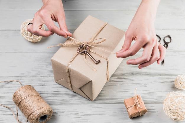 Chaîne de cravate mains féminines sur cadeau emballé sur un bureau en bois Photo gratuit