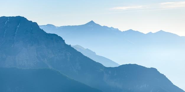 Chaîne de montagnes bleu tonique lointaine des majestueuses alpes européennes avec brouillard et brouillard dans la vallée ci-dessous Photo Premium