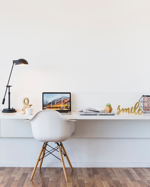 Une chaise blanche vide devant le bureau avec ordinateur portable et pièce maîtresse Photo gratuit