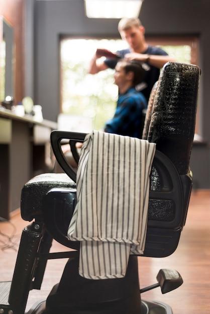 Chaise de coiffeur avec homme défocalisé en arrière-plan Photo gratuit