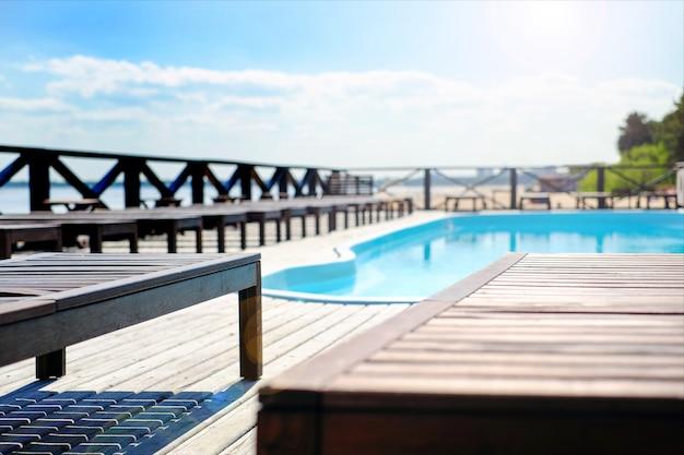 Chaises longues en bois au bord de la piscine. près de la mer. Photo Premium