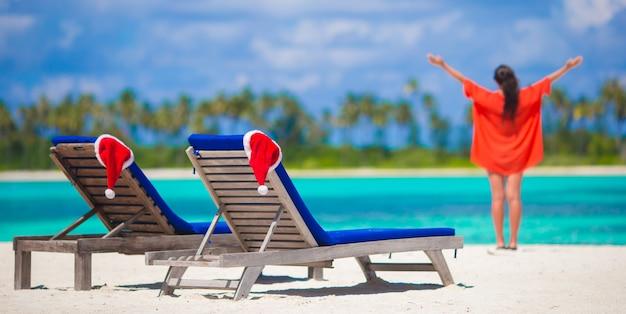 Chaises longues avec des chapeaux de santa rouges et jeune femme pendant des vacances tropicales Photo Premium