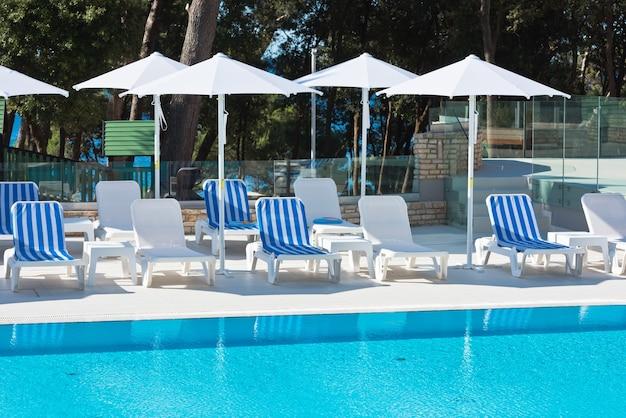 Chaises De Piscine D'hôtel Avec Vue Sur La Mer. Tir D'été Photo Premium