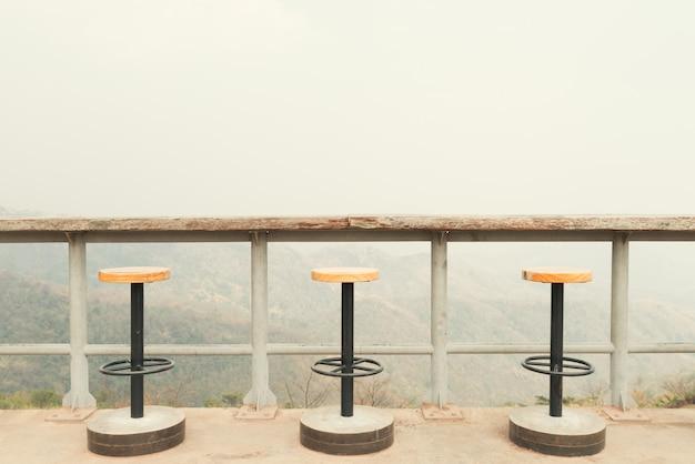 Chaises sur terrasse ensoleillée avec vue sur la baie et décoration de maison contemporaine. Photo Premium
