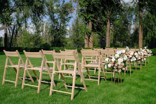 Chaises vides en bois blancs dans une rangée et bouquets de fleurs sur l'herbe verte. décorations de mariage Photo Premium
