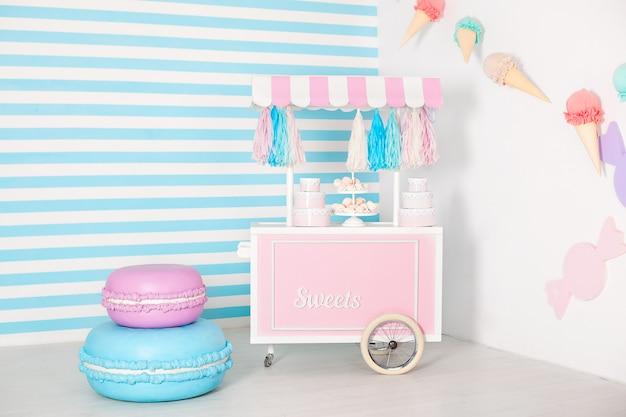 Chambre d'enfants avec mur rayé bleu. zone de photo de stand de bonbons avec de gros macarons, des bonbons et des guimauves. chariot à glace. chambre décorée pour un anniversaire. panier avec candy bar. Photo Premium