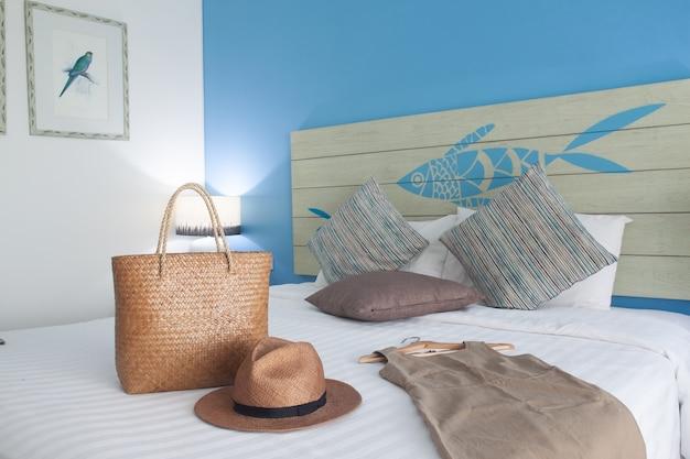 Chambre Lumineuse Moderne Avec Vêtements D'été, Robe, Chapeau Et Sac Sur Lit Blanc. Photo Premium