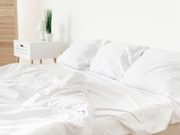 Chambre moderne lumineuse avec des draps blancs Photo gratuit