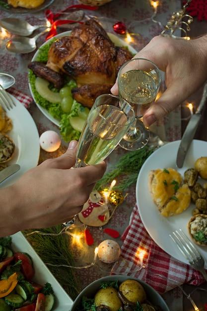 Champagne dans les mains. table de noel nouvel an. Photo Premium