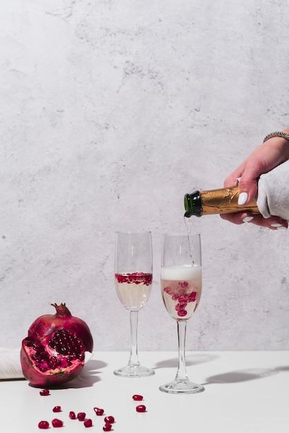 Champagne Verser Dans Le Verre Avec La Grenade Photo gratuit