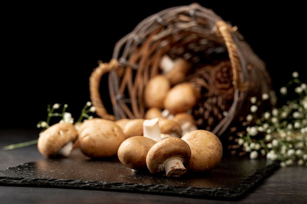 Champignons sur une assiette en pierre noire avec un panier tricoté brun Photo gratuit