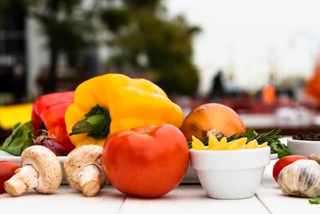 Champignons crus; tomate; poivrons; ail; oignon; sur le bureau blanc Photo gratuit