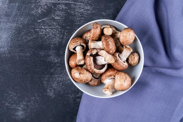 Champignons Dans Un Bol Sur Un Tissu Violet Sur Une Table Sombre Photo gratuit