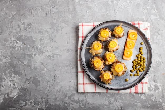 Champignons frits farcis au fromage, kumquats et pois verts sur fond gris Photo Premium